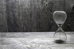Ampulheta com grões de areia pretas no fundo de madeira do vintage foto de stock