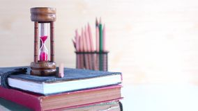 Ampulheta e lápis colocados em livros de texto na tabela branca vídeos de arquivo