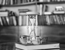 Ampulheta, livro velho e monóculos na tabela de madeira, biblioteca no fundo Conceito dos atributos dos cientistas hourglass foto de stock royalty free