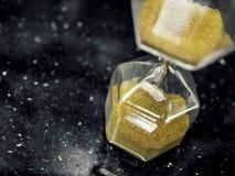 Ampulheta moderna do hexágono com a semente dourada da areia imagens de stock royalty free