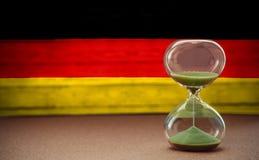 Ampulheta no fundo da bandeira alemão, no conceito do tempo e nos países, espaço para o texto foto de stock royalty free