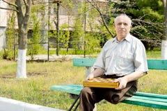 Amputé supérieur s'asseyant sur un banc de parc Images libres de droits