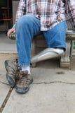 Amputado de la pierna que se sienta en banco con las manos por los lados, piernas cruzadas imagen de archivo libre de regalías