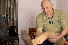 Amputado que olha seu pé protético novo Imagem de Stock