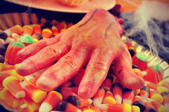 Amputated hand and Halloween candies, filtered Stock Image