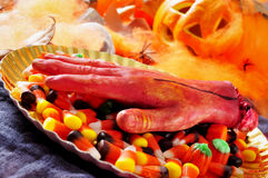 Amputated hand and Halloween candies Stock Images