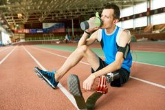 Amputee Sportsman Sitting on Stadium Track royalty free stock image