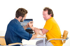 Amputee works with medical professional at table. Testing function of arm-prosthesis with patient. Stock Photos