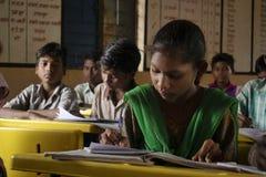 AMRAVATI, MAHARASHTRA, ΙΝΔΙΑ, τον Αύγουστο του 2018, κορίτσι που γράφει στο γραφείο της στο δημοτικό σχολείο στο χωριό Ghuti, Dha στοκ φωτογραφία