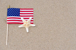 Amrican flag with starfish on the sandy beach Stock Images