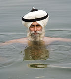 Amritsar - Sikh man bathing in sacred pool. A sikh man bathing in the sacred waters of Harmandir Sahib at the Golden Temple of Amritsar in the Punjab region of Stock Images