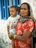 Amroha, Uttar Pradesh, INDIEN - 2011: Ländliche indische Frau mit Kind in den Händen und im roten Sari Lizenzfreie Stockfotos