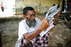 Amroha, Uttar Pradesh, la India - 2011 - un hombre se sienta en el paso, absorbente en periódico de la lectura Foto de archivo