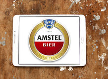 Amstel beer logo. Logo of beer drinks company amstel on samsung tablet on wooden background Stock Photography
