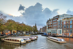 Amstel canal boats Amsterdam. Beautiful cityscape view towards the Mint tower Munttoren with tourist canal boats at the Amstel river in Amsterdam, the royalty free stock photo