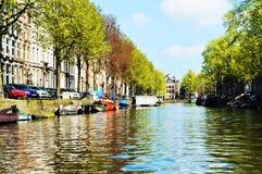 Amstel flod i Amsterdam, Nederländerna, Europa och färgrika byggnader Royaltyfri Bild