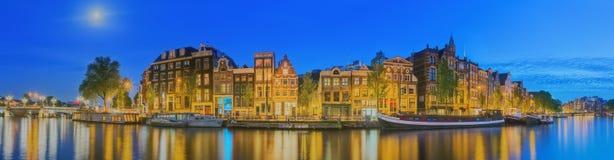 Amstel flod, kanaler och nattsikt av den härliga Amsterdam staden Nederländerna Royaltyfria Foton