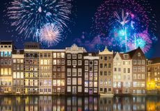 River, traditional old houses and boats, Amsterdam. Amstel river, canals and boats against night cityscape of Amsterdam with fireworks and reflection on water stock images
