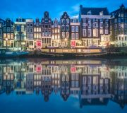 River, traditional old houses and boats, Amsterdam. Amstel river, canals and boats against night cityscape of Amsterdam, Holland Netherlands stock image