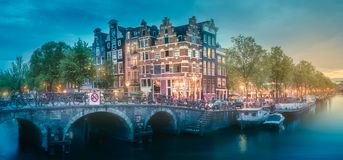 River, traditional old houses and boats, Amsterdam. Amstel river, canals and boats against night cityscape of Amsterdam, Holland Netherlands royalty free stock images
