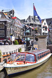 Amstel river with Tour boat. Canal at Amsterdam city, Netherlands. Excursion boats and cityscape of Amsterdam at a a sunny day with blue sky stock photos
