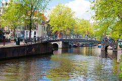 AMSTERDÃO, PAÍSES BAIXOS 27 DE ABRIL: Canal de Amsterdão com as bicicletas ao longo da ponte no Dia do rei em Amsterdão, os Paíse Imagens de Stock Royalty Free