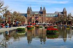 AMSTERDÃO, PAÍSES BAIXOS - 22 DE ABRIL DE 2017: Museu Nacional de Rijksmuseum com sinal de I Amsterdão e tulipas em refletir fotografia de stock royalty free