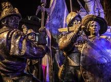 AMSTERDÃO, PAÍSES BAIXOS - 19 DE DEZEMBRO DE 2015: As figuras de bronze dos soldados no quadrado central da cidade iluminaram-se  Imagens de Stock Royalty Free