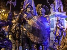 AMSTERDÃO, PAÍSES BAIXOS - 19 DE DEZEMBRO DE 2015: As figuras de bronze dos soldados no quadrado central da cidade iluminaram-se  Fotografia de Stock Royalty Free