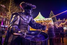 AMSTERDÃO, PAÍSES BAIXOS - 19 DE DEZEMBRO DE 2015: As figuras de bronze dos soldados no quadrado central da cidade iluminaram-se  Fotos de Stock Royalty Free