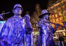 AMSTERDÃO, PAÍSES BAIXOS - 19 DE DEZEMBRO DE 2015: As figuras de bronze dos soldados no quadrado central da cidade iluminaram-se  Fotos de Stock