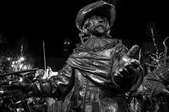 AMSTERDÃO, PAÍSES BAIXOS - 19 DE DEZEMBRO DE 2015: As figuras de bronze dos soldados no quadrado central da cidade iluminaram-se  Imagem de Stock Royalty Free