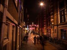 AMSTERDÃO, PAÍSES BAIXOS - 20 DE JANEIRO DE 2016: Ruas da noite de Amsterdão com as silhuetas borradas dos transeuntes o 20 de ja Imagens de Stock Royalty Free