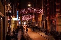 AMSTERDÃO, PAÍSES BAIXOS - 20 DE JANEIRO DE 2016: Ruas da noite de Amsterdão com as silhuetas borradas dos transeuntes o 20 de ja Fotos de Stock