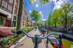 Amsterdão, Países Baixos - 10 de julho de 2015: Ponto de vista dos motociclistas como bicycling através das ruas da cidade em um  Imagens de Stock