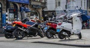 Amsterdão, Países Baixos - 19 de julho de 2014: Uma fileira das bicicletas motorizadas/'trotinette's estacionou acima em Amsterdã Fotografia de Stock