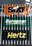 AMSTERDÃO, PAÍSES BAIXOS - 18 DE JULHO DE 2018: Quadro de avisos do carro alugado de SIXT Hertz Europcar na cerca de aço no aerop fotos de stock royalty free