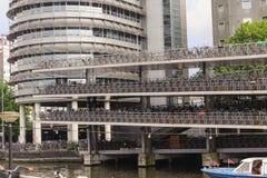 AMSTERDÃO, PAÍSES BAIXOS - 12 DE JUNHO DE 2012: O andar múltiplo bicycles o lugar de estacionamento em Amsterdão O estacionamento Fotografia de Stock Royalty Free