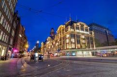 Amsterdão, Países Baixos - 7 de maio de 2015: Loja de De Bijenkorf da visita do turista no quadrado da represa Imagem de Stock Royalty Free