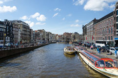 Amsterdão, Países Baixos - 7 de maio de 2015: Os barcos de passageiro no canal visitam na cidade de Amsterdão Imagem de Stock Royalty Free