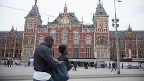 AMSTERDÃO, PAÍSES BAIXOS - 18 DE OUTUBRO DE 2016: Povos na frente da estação de trem central de Amsterdão, tempo-lapso filme