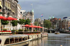 Amsterdam. Tour boats in a canal outside a hotel/restaurant in Amsterdam stock photography