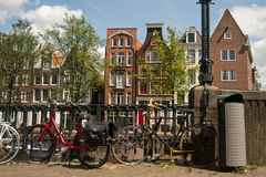 Amsterdam bikes at sidewalk with houses on background Stock Photo