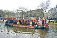 AMSTERDAM - APRIL 30: Amsterdam canals full of boats and people Royalty Free Stock Photo