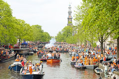 AMSTERDAM - APRIL 26: Amsterdam canals full of boats and people Stock Photo