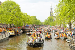 AMSTERDAM - APRIL 26: Amsterdam canals full of boats and people Royalty Free Stock Photo