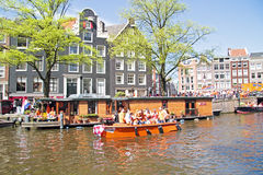 AMSTERDAM - APRIL 30: Amsterdam canals full of boats and people Royalty Free Stock Images