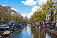 AMSTERDAM-APRIL 30: Amsterdam cityscape with row of cars, bikes and boats parked along the canal during the sunny day. Stock Photos