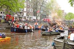 AMSTERDAM - 26. APRIL: Amsterdam-Kanäle voll von Booten und von Leuten Stockbilder