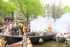 AMSTERDAM - 26. APRIL: Amsterdam-Kanäle voll von Booten und von Leuten Lizenzfreies Stockfoto